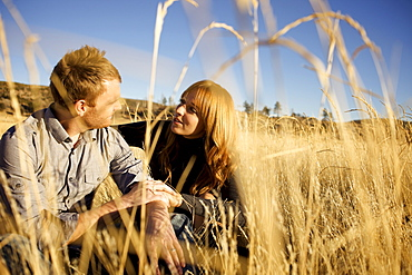 Couple sitting on the ground of an open field look at each other and smile.