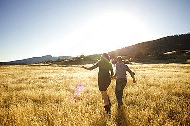 Couple hold hands and run together in an open field.