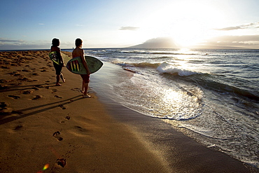 Two men watching the surf at sunset with their skimboards in their arms.