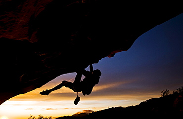 A young man climbs a boulder problem during a sunset overlooking the ocean in Santa Barbara, CA.