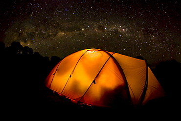 A tent illuminates the night as the Milky Way Galaxy floats above in a starry sky on Mt. Kilimnajaro.