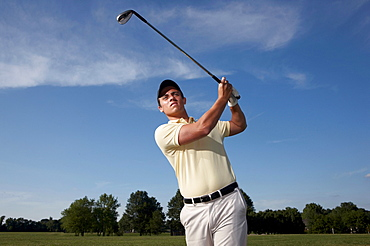 A male golfer swinging his club.