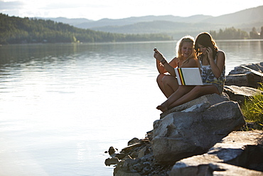 Two young women talk while texting and chatting on a computer on a sunny day at the lake.