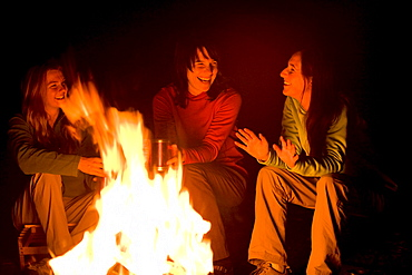 Three women talk and laugh together around a campfire.
