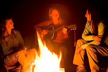 Two women listen, as a third plays the guitar beside a campfire.