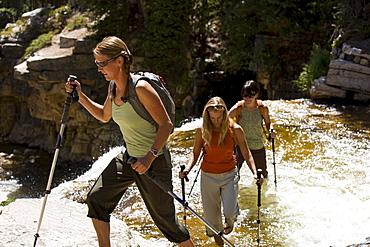 Three women wade across Utah's Provo River.