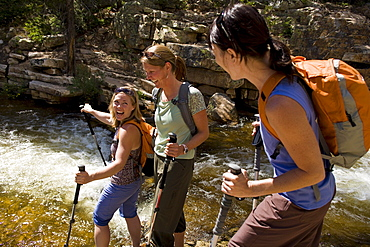 Three women talking and laughing during a hike along Utah's Provo River.