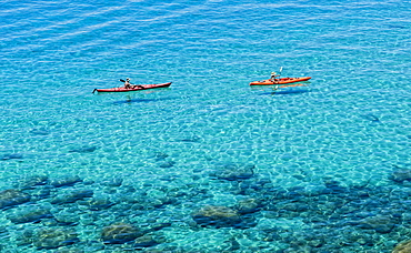 A pair of kayakers is out for a morning paddle along the pristine shores of Lake Tahoe, Nevada.