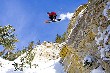 A skier catches some air off a large cliff at Snowbird, Utah