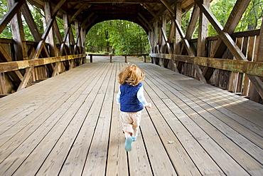 A little girl runs across a covered bridge.