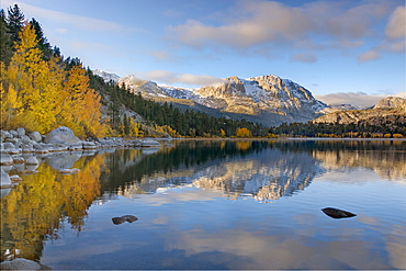 Yellow aspens clouds and a mountain  reflecting in June Lake in the fall in the Sierra mountains of California
