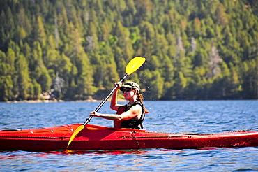 A woman kayaks on Caples Lake near Kirkwood, California in the summer.