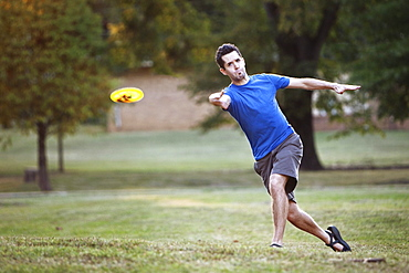 A man makes a forehanded throw playing disc golf.
