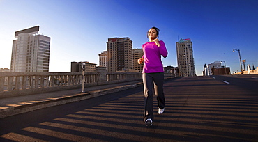 A teenage girl runs downhill on a street in downtown Birmingham, Alabama.