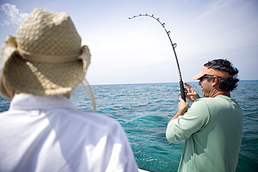 A fisherman reels in a fish as his pole bends down during the fight.