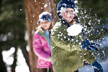 A boy and girl enjoy a snowball fight in Lake Tahoe, California.