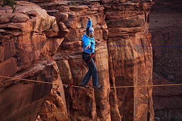 A female highliner walks across a highline at the Fruit Bowl in Moab, Utah, USA.