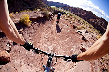 Mountain bikers riding on a trail overlooking the Colorado River near Moab Utah.