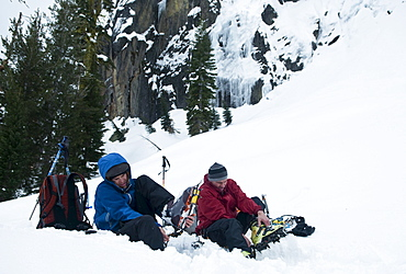 Two men put crampons on their boots before ice climbing in Truckee, California.