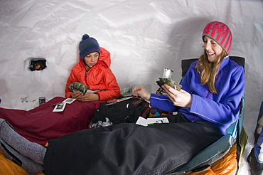 Boy and girl playing cards in snow cave, Silverton, Colorado.