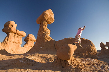 Young girl jumping off rocks in Goblin Valley State Park, Hanksville, Utah.