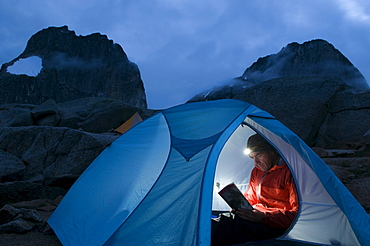 Man reading guidebook by headlamp in tent, Bugaboo Provincial Park, Radium, British Columbia, Canada.