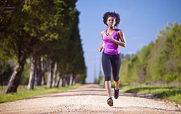 A woman runs on a dirt road lined with trees.