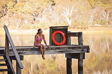 Sabina Allemann, 49 years old is sitting by Lake Catani wearing a bikini swimsuit early on 26th January 2012, Mount Buffalo National Park, Victoria, Australia.