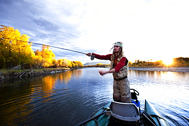 A fly fisher casting his line out of a boat while fly fishing on the Yellowstone River surrounded by fall colors in Bozeman, Montana.