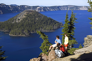 Hikers along cliff trail near lake.