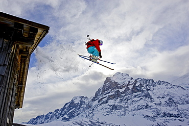 A young man skis off the roof of an alpine hut in Grindalwald, Switzerland.