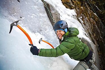 An adventurous female wearing a green jacket climbs a frozen icy waterfall near Pemberton, British Columbia, Canada.