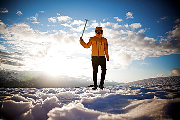 A climber holds up his ice axe while walking on a snow covered alpine ridge.