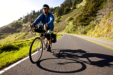 A male cyclist rides his touring bike down the Pacific Coast Highway near Jenner, California on April 12, 2013.