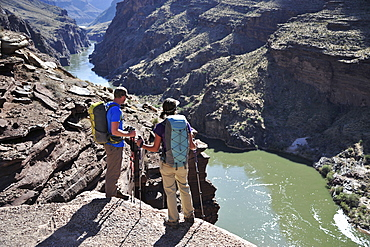 Hikers overlook the Colorado River as they exit the Deer Creek Narrows in the Grand Canyon outside of Fredonia, Arizona November 2011.  The 21.4-mile loop starts at the Bill Hall trailhead on the North Rim and descends 2000-feet in 2.5-miles through Coconino Sandstone to the level Esplanada then descends further into the lower canyon through a break in the 400-foot-tall Redwall to access Surprise Valley.  Hikers connect Thunder River and Tapeats Creek to a route along the Colorado River and climb out Deer Creek.