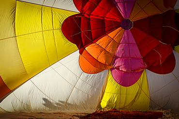 Crews work carefully, inflating their hot air balloons for launch. The Albuquerque International Balloon Fiesta takes place in Albuquerque, New Mexico each year drawing in participants and spectators from across the globe. Highlights include an early morning dawn patrol, followed by mass ascencion of aircraft and an evening glow which all take place at the Balloon Fiesta Park throughout the week long event.