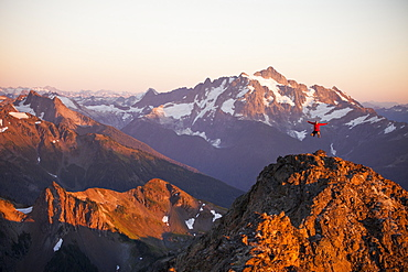 A hiker jumps into the air from a rocky ridge in the North Cascade Mountains with Mount Shuksan in the background, North Cascades National Park, Washington, United States