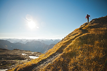A hiker follows a footbed to the top of a mountain ridge, North Cascades National Park, Washington, United States