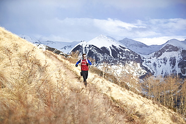 Adult male trail running through a grassy trail high in the mountains above Telluride Colorado on a beautiful spring afternoon, Telluride, Co, USA