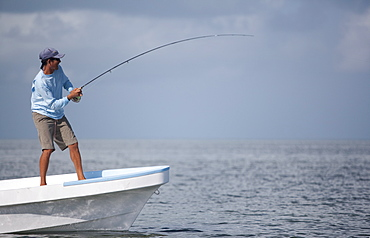 fly rod bends as a fisherman reels in while standing on the bow of his boat, San Pedro, Belize