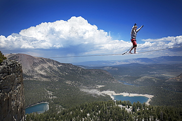 Male highliner in cowboy hat walks a 125 foot highline over a lake in a gap on top of Mammoth Crest, Mammoth, California, United States