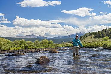 Wading through the river for the next hole high in the mountains of Colorado, Colorado, USA