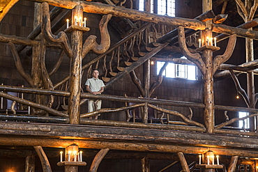 A woman standing next to the intricate logwork inside the Old Faithful Lodge in Yellowstone National Park, Wyoming, Yellowstone, Wyoming, usa