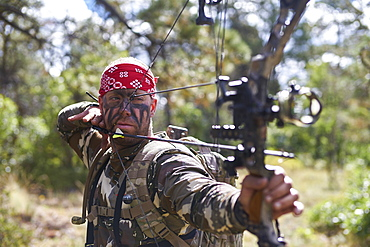 Bow Hunter with red bandana aiming compound bow, Pagosa Springs, CO, USA