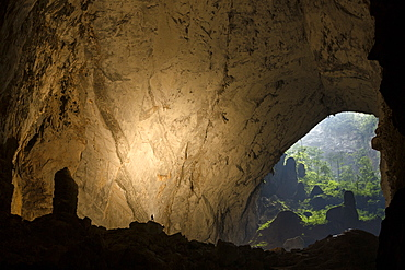 A cave explorer illuminates a large passage looking out towards the second doline in Hang Son Doong, Vietnam.
