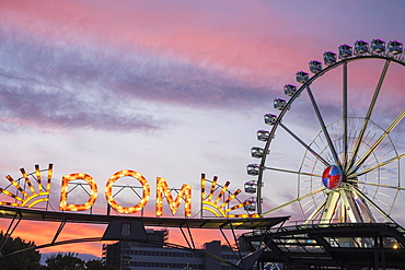 Illuminated entrance to Hamburger DOM funfair and ferris wheel at sunset, St. Pauli, Hamburg, Germany