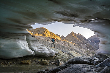 A woman hiking in front of glacial snout of ice in Titcomb Basin in the Wind River Range, Bridger Teton National Forest,  Pinedale, Wyoming.