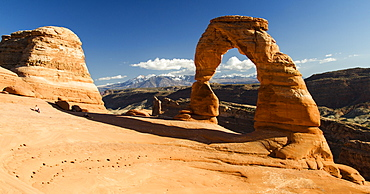 People relaxing while viewing  Delicate Arch with the La Sal mountain range in the background, Arches National Park, Utah.