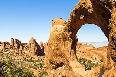 A man standying in Double O arch as he looks at the horizon at the Arches National Park in Utah near Moab.