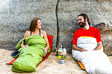 Man and a woman on the beach in sleeping bags laughing with a stove heating water.